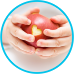 Baby hands holding apple with heart cut out